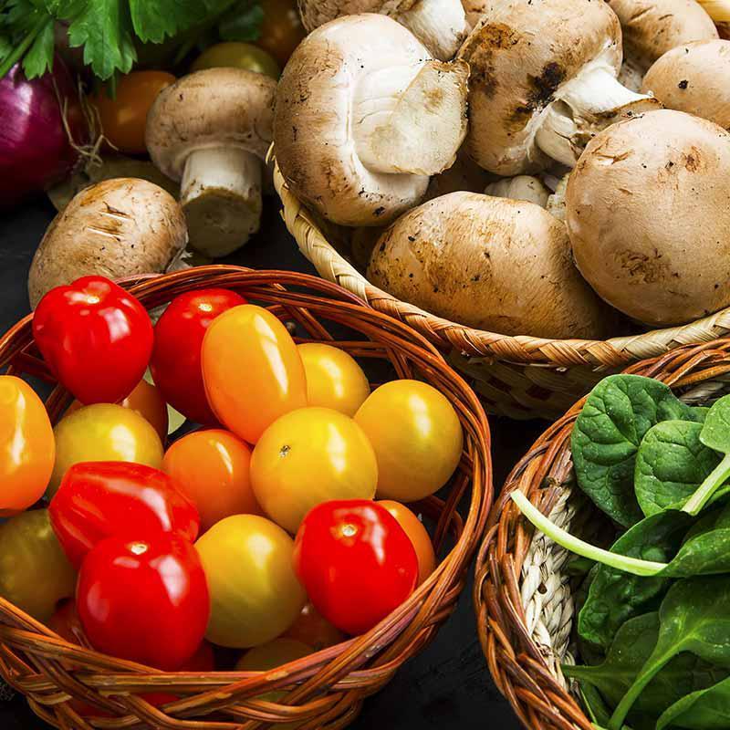 foto van kerstomaten, champignons, spinazie en rode ui